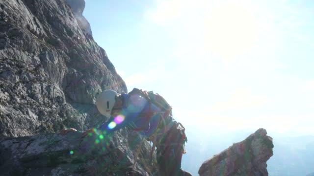 vidéos et rushes de mountaineer ascends ridge line above distant mountains - harnais de sécurité