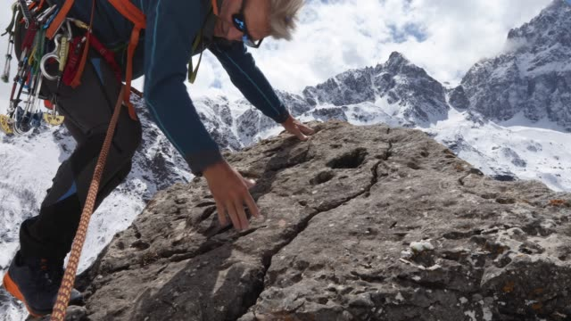 mountaineer ascends rock buttress, placing protection - ウィンターコート点の映像素材/bロール