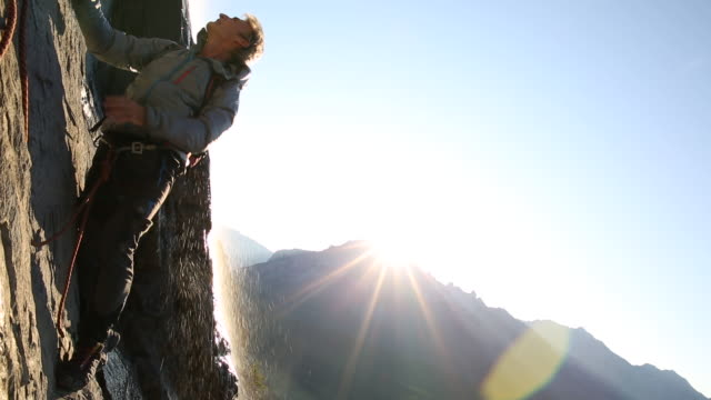 mountaineer ascends rock face above mountains, sunrise - fels stock-videos und b-roll-filmmaterial