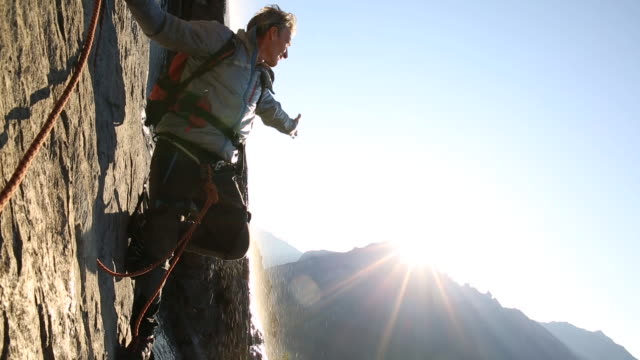 Mountaineer ascends rock face above mountains, sunrise