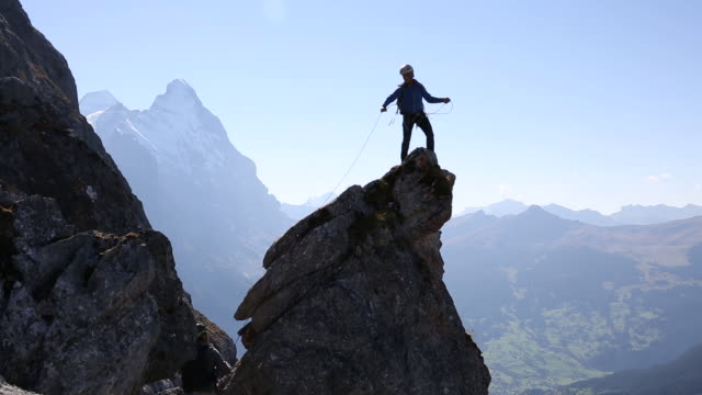 Mountaineer ascends rock pinnacle in high mountains