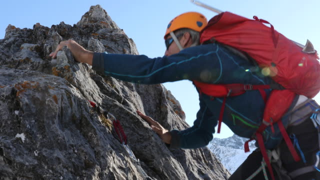 Mountaineer ascends rock ridge, nears summit