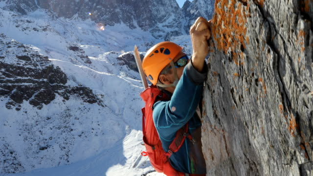 mountaineer ascends rock ridge, nears summit - tracking shot stock videos & royalty-free footage
