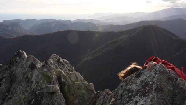 vídeos de stock, filmes e b-roll de mountaineer ascends rock ridge, nears summit - gancho de alpinismo