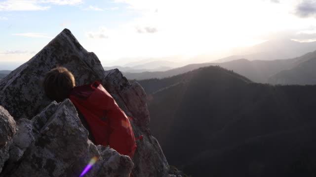 vídeos de stock, filmes e b-roll de mountaineer ascends rock ridge, nears summit - batalha conceito