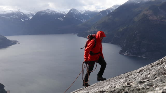 mountaineer ascends rock slab route above sea, mountains - moving up stock videos & royalty-free footage