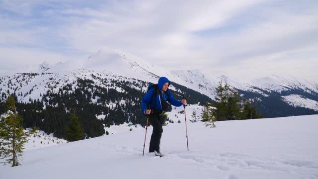 vidéos et rushes de l'alpiniste monte la neige, vers le sommet de la montagne - endroit isolé