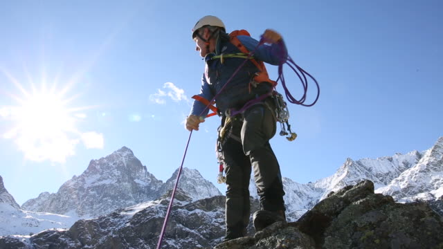 Mountaineer ascends steep rock pinnacle above valley, mtns