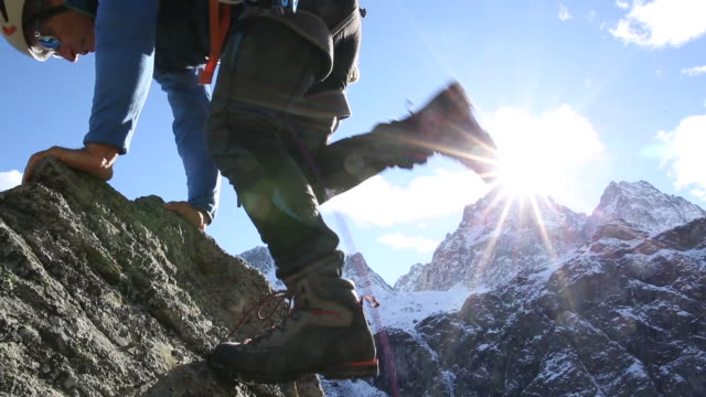 mountaineer ascends steep rock pinnacle above valley, mtns - helmet stock videos & royalty-free footage