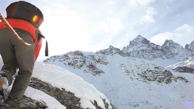 Mountaineer ascends to snowy summit, stretches arms outwards