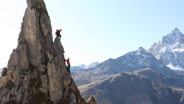 mountaineer belays teammate on steep pinnacle climb - climbing stock videos & royalty-free footage