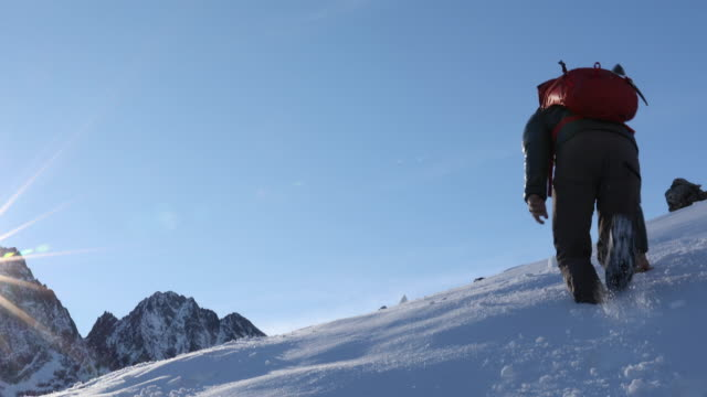 Mountaineer bounds up snow slope, near summit