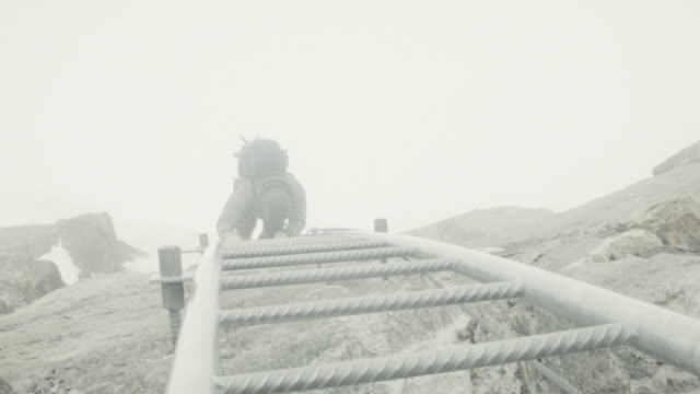 Mountaineer climbing ladder up rocky surface during snow storm in Swiss Alps