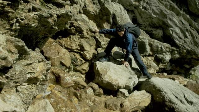 A mountaineer climbing over rocks in rugged terrain.