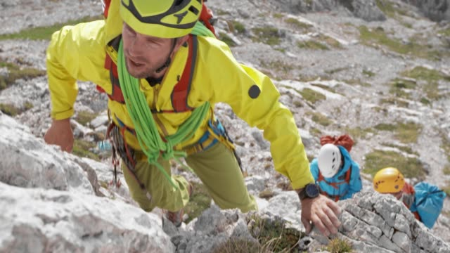 mountaineer climbing up a rock in the mountains in sunshine - slovenia stock videos & royalty-free footage