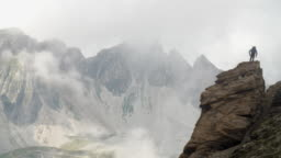 A mountaineer climbs a rock stack on a high mountain ridge as bad weather closes in.