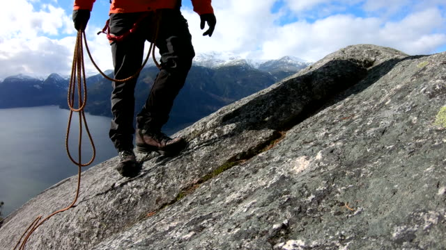 登山家は、登山ロープで、花崗岩の尾根の紋章を登ります - 冠雪点の映像素材/bロール