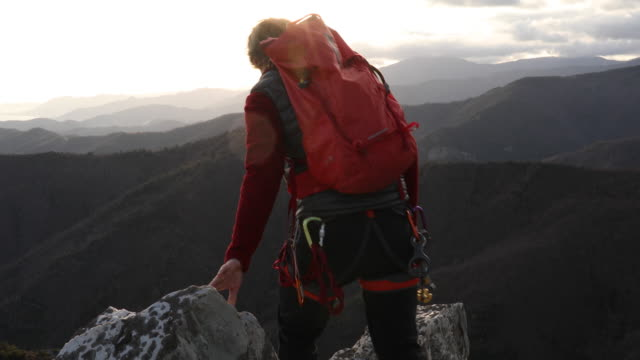 mountaineer climbs onto rock ridge, looks down to route below - animal skin stock videos & royalty-free footage