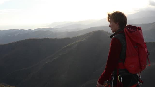 Mountaineer climbs onto rock ridge, pulls rope tight
