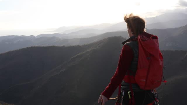 vídeos de stock, filmes e b-roll de mountaineer climbs onto rock ridge, pulls rope tight - gancho de alpinismo