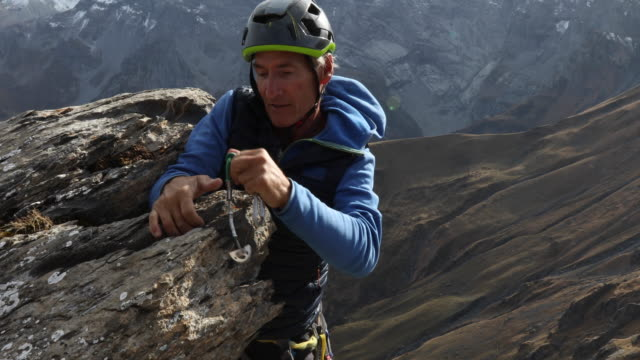 mountaineer climbs vertical cliff, places protection, mountains - only mature men stock videos & royalty-free footage