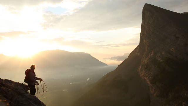 Mountaineer coils rope at cliff edge, sun rises behind