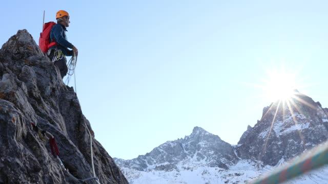 Mountaineer coils rope on mountain summit
