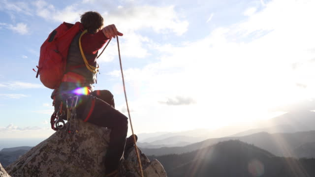 mountaineer coils rope on rock summit, above mountains, sea - カラビナ点の映像素材/bロール
