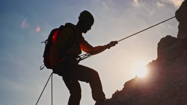 mountaineer descending the mountain in sunshine - climbing rope stock videos & royalty-free footage