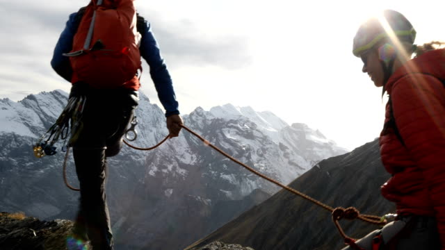 Mountaineer descends vertical cliff, past protection, mountains