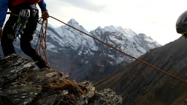 mountaineer descends vertical cliff, past protection, mountains - rope stock videos & royalty-free footage