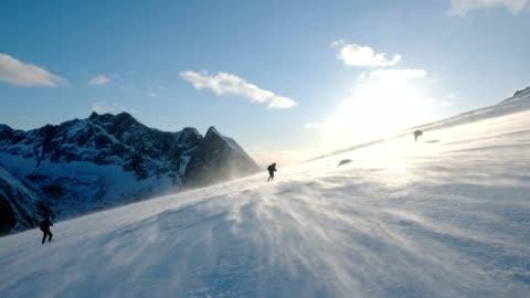 vídeos y material grabado en eventos de stock de grupo montañista trekking en montaña pendiente con blizzard - deporte de riesgo