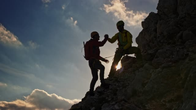 mountaineer helping rope team member climb to the top of the mountain in sunshine - climbing rope stock videos & royalty-free footage