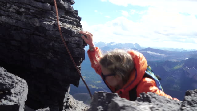 Mountaineer helps young woman mountaineer to ascend steep bluff