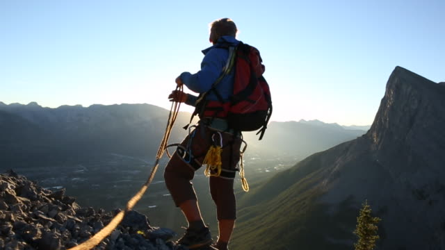 Mountaineer leaps to edge of rock cliff, looks down and pulls in rope