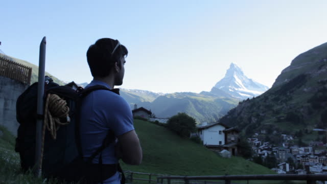 mountaineer looking at village of zermatt and matterhorn peak. - hill stock videos & royalty-free footage