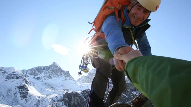 Mountaineer offers helping hand to companion, from mountain summit