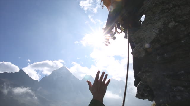 Mountaineer offers helping hand to companion, on cliff
