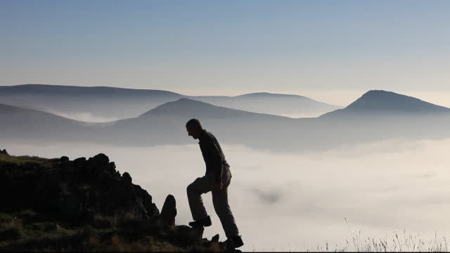 A mountaineer on Red Screes in the Lake District, above valley mist caused by a temperature inversion, UK.