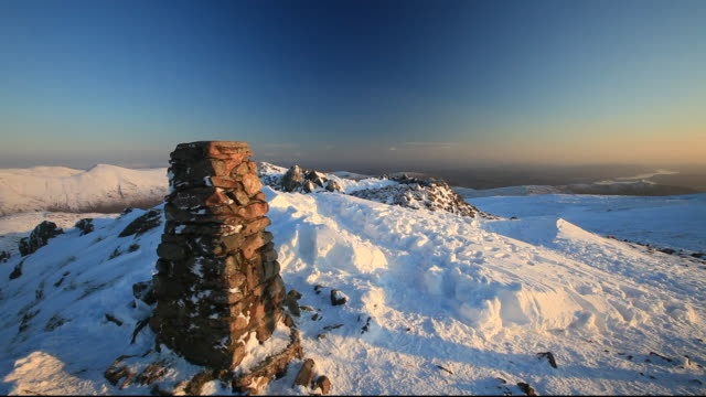 A mountaineer on Red Screes in the Lake District,Cumbria, UK, in mid winter, looking towards Windermere.