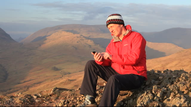 A mountaineer on the summit Wansfell in the Lake District National Park, Cumbria, UK, talking on a cell phone.