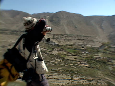 ms, pan, mountaineer photographing mountains, mustang- himalaya, nepal - solo uomini di età media video stock e b–roll