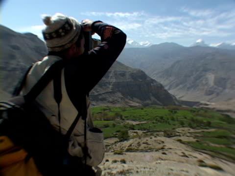 ms, mountaineer photographing mountains, rear view, mustang- himalaya, nepal - solo uomini di età media video stock e b–roll