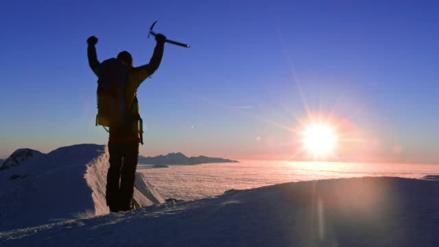 SLO MO Mountaineer raising his hands on mountain top at sunset