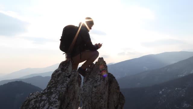 mountaineer reaches pinnacle summit, takes phone pic - 携帯情報端末点の映像素材/bロール