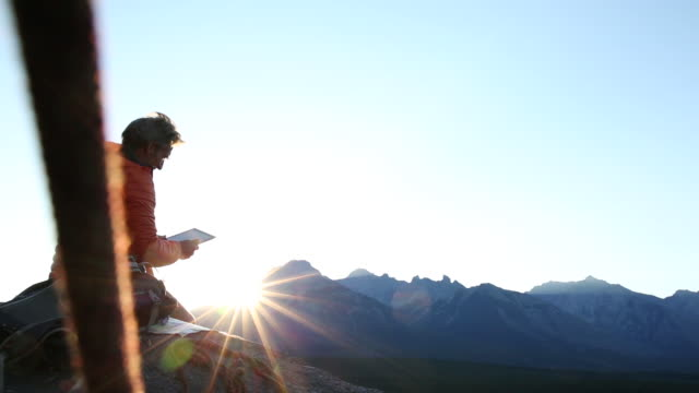 Mountaineer relaxes on rock ledge, consults digital tablet, then takes pic