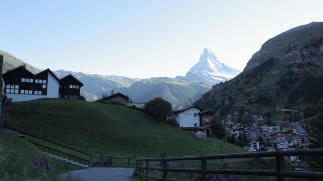Mountaineer running out of village of Zermatt with Matterhorn peak in background.