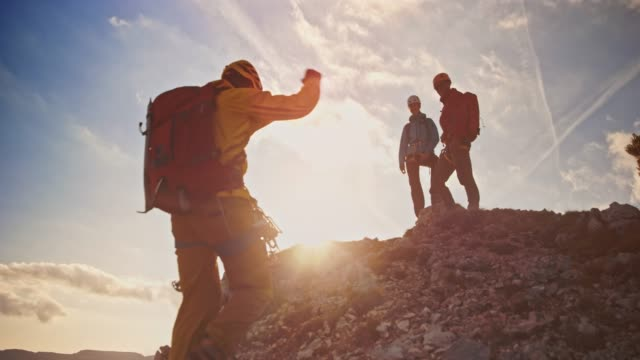 mountaineer shaking hands with fellow mountaineers waiting on the mountain top in sunshine - hiking stock videos & royalty-free footage