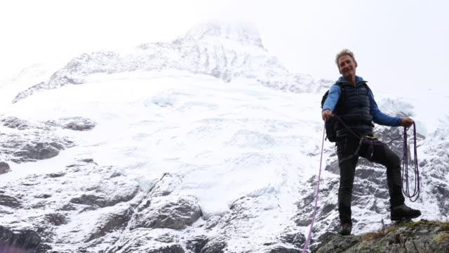 mountaineer stretches rope tight to teammate, mountains - ein mann allein stock-videos und b-roll-filmmaterial