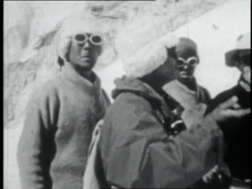 vidéos et rushes de mountaineer talking to other mountaineers wearing snow goggles on mount everest's lower slopes / nepal - 1952